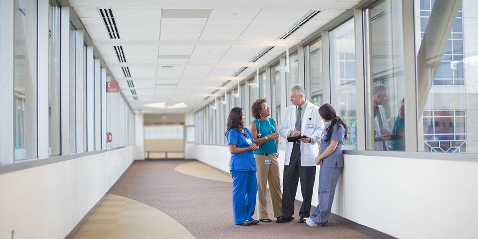 Doctor and nurses talking in hospital hallway